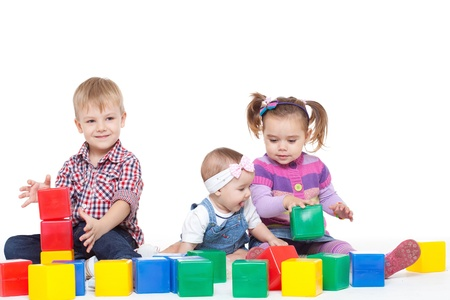 Foto de Small children sit on a floor and play with multi-coloured cubes - Imagen libre de derechos