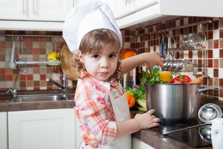 Little girl plays the cook and makes a dinner