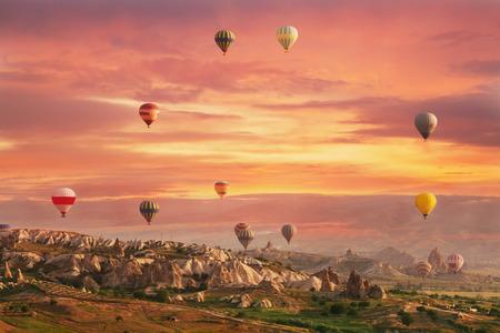 Photo pour Multi-colored air shata fly over rocks in Cappadocia at sunrise - image libre de droit