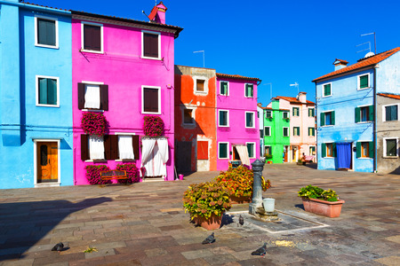 A small courtyard in Burano, with colored walls of houses, a column for water and flowers, Italy