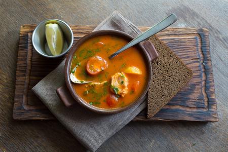 Marmitako soup in a ceramic bowl on a wooden board