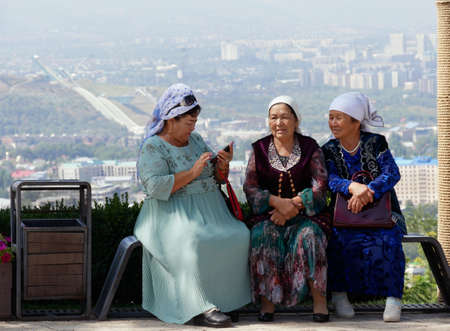 Almaty, Kazakhstan - 3 September 2019: Three senior women are resting on a view point in Almaty while one of them is using her mobile phone.