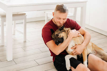 Photo for A man of European appearance hugs a large dog at home. Love for pets and dogs - Royalty Free Image