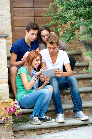 Laughing teenagers looking at the touchpad screen outdoors ,Italy