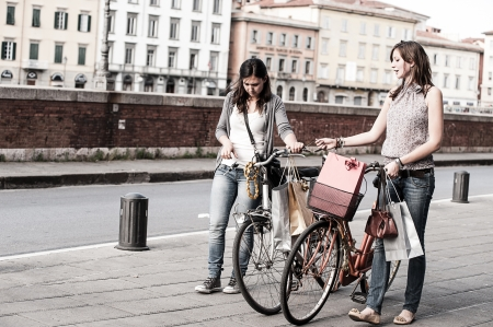 Photo pour Two Beautiful Women Walking in the City with Bicycles and Bags,Italy - image libre de droit
