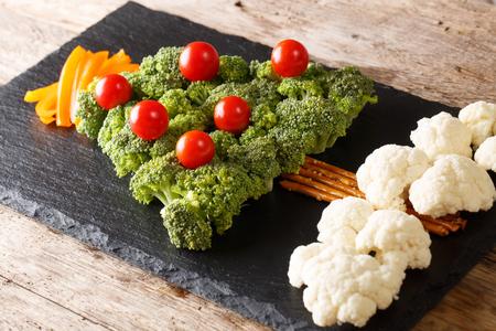 Christmas tree of broccoli, cauliflower, tomato, pepper closeup on table. Vegetarian menu. horizontal