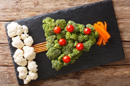 Christmas tree of broccoli, cauliflower, tomato, pepper closeup on table. Vegetarian menu. Horizontal top view from above