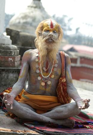 Nepal, Kathmandu Valley, october 11, 2010. Shaiva sadhu (holy man) seeking alms in front of a temple in Pashupatinath