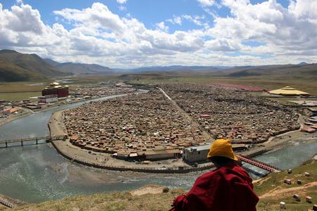 A Tibetan monk overlooking the Yarchen Gar (Yaqen Orgyan Temple) in Baiyu (or 'Pelyul') county, Garze, China - in March 2015.