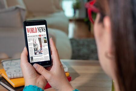 Foto de Online news on a mobile phone. Close up of the page of a businesswoman reading news or articles on a smartphone screen application. Smartphone with hand. Mockup website. Newspaper and Internet portal. - Imagen libre de derechos