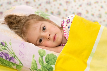 Photo pour The little girl in bed. A little girl lying in bed with sad eyes - image libre de droit
