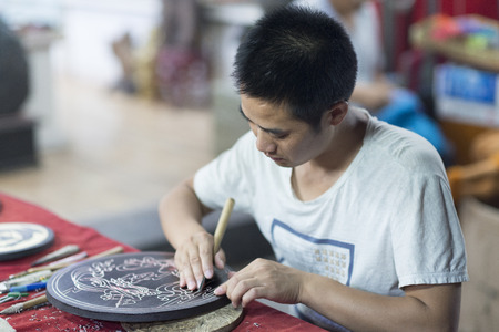 Photo for Dunhuang, China - 08 06 2016: A craftsman depicts Dunhuang culture through wood carvings. Chinese artist chinese carving figures into a round of wood - Royalty Free Image