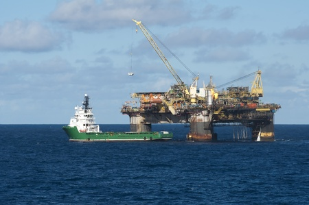 offshore oil rig tranfering some container to supply vessel, in Campos Basin, Brazil.