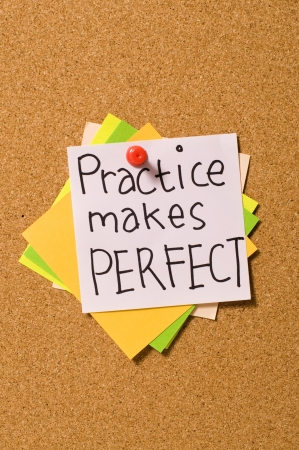 Practice Makes Perfect write on the paper on the cork board