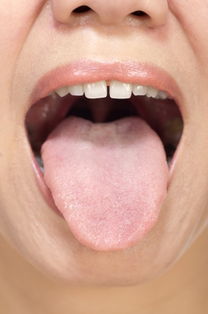 Woman stick ones tongue out isolated in white