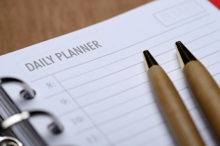 Open agenda with pen on wooden background. Daily planner concept
