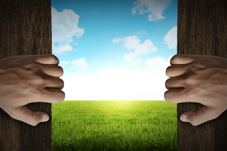 Man hand open door into green grass meadow