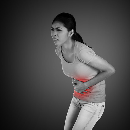 Young asian woman have stomach ache, with uneasy face