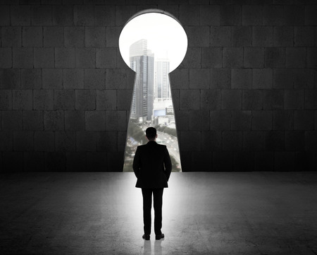 Concept of success business man looking through key hole