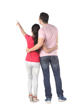 Young asian couple pointing something isolated over white background