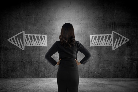 Foto de Business woman has to choose between two way. Business option conceptual - Imagen libre de derechos