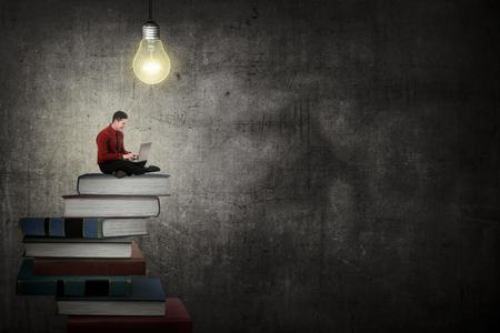 Foto de Asian business person working with laptop sit on top of book. Idea and knowledge concept - Imagen libre de derechos