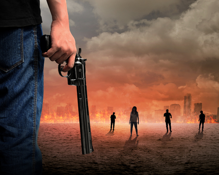 Man hand holding gun with zombie and burn city backgroundの写真素材