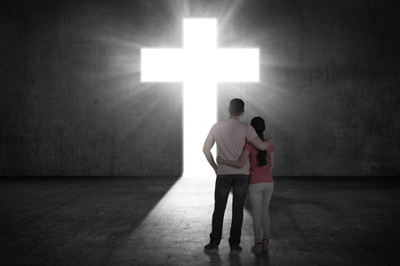 Photo for Young couple looking the shining cross on the wall. Religious concept - Royalty Free Image