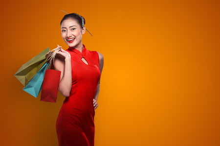 Photo pour Chinese woman wearing cheongsam hold shopping bag. Happy chinese new year - image libre de droit