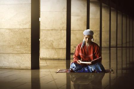 Photo pour Religious muslim man reading holy koran inside the mosque - image libre de droit
