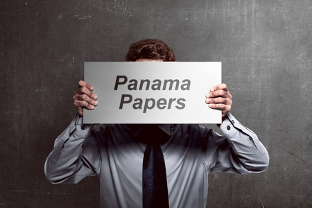 Image of business man holding board cover his face with panama papers text