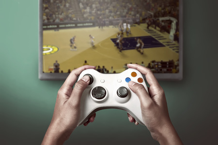 Photo pour Hand holding game console controller playing sport game on the television - image libre de droit