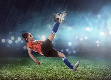 Foto de Asian woman football player kick ball on the stadium - Imagen libre de derechos