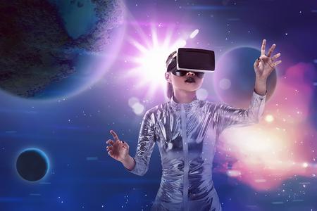 Photo pour Pretty asian woman wearing silver latex jumpsuit and VR headset inside virtual world. Virtual reality concept - image libre de droit
