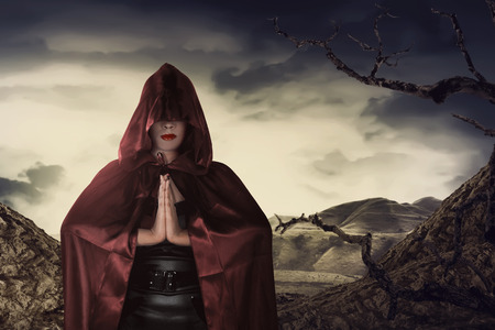 Beautiful asian witch woman with red cloak praying in hill