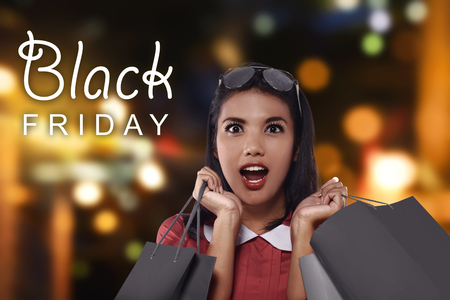 Happy asian woman with shopping bags on Black Friday celebrationの写真素材