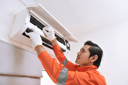 Photo for Young asian male technician repairing air conditioner at home - Royalty Free Image