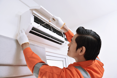 Photo pour Young asian male technician repairing air conditioner with screwdriver at home - image libre de droit