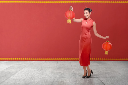 Photo pour Young chinese woman in a traditional clothing holding red lanterns with red wall background - image libre de droit