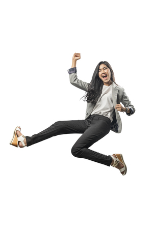 Foto de Successful asian business woman jumping and raised arm to the air posing isolated over white background - Imagen libre de derechos