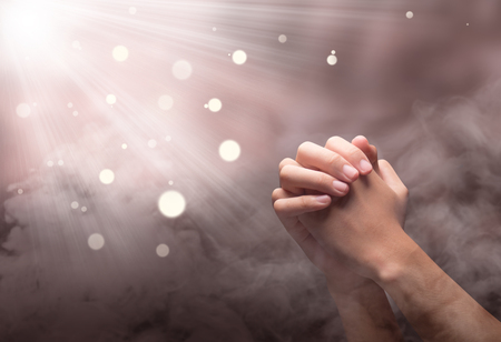 Photo for Male hands in praying position with ray over blurry background - Royalty Free Image