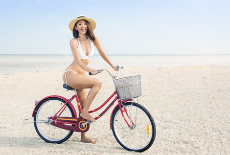 Photo for Asian sexy girl with hat and bikini riding bicycle on the beach. Summer vacation - Royalty Free Image