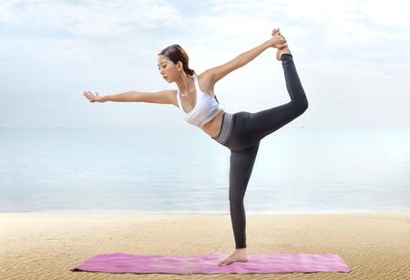 Photo pour Asian healthy woman practicing yoga on the carpet in beach. Healthy concept - image libre de droit