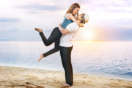 Photo pour Happy asian man in hat hugging his girlfriend on the beach. Summer vacation - image libre de droit