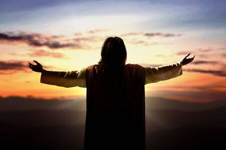 Foto de Rear view of Jesus Christ raised hands and praying to god with a sunset sky background - Imagen libre de derechos