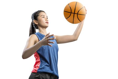 Foto de Asian woman basketball player holding the ball isolated over white background - Imagen libre de derechos