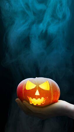 Foto de Hand holding Jack-o-Lantern with a dark smoke background. Stories template for Halloween - Imagen libre de derechos