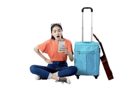 Photo pour Asian woman sitting with a suitcase holding mobile phone isolated over white background - image libre de droit
