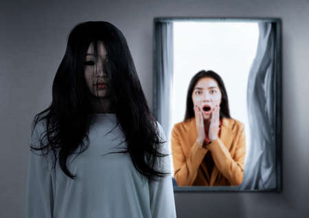 Photo pour Asian businesswoman scared looking at a scary ghost woman in the abandoned house. Halloween concept - image libre de droit