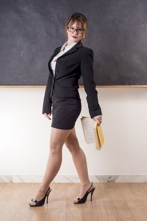 Sexy teacher with blackboard looking you with a book
